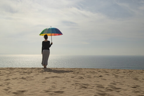 Woman with colorful umbrella standing at the beach, rear view - KBF00552