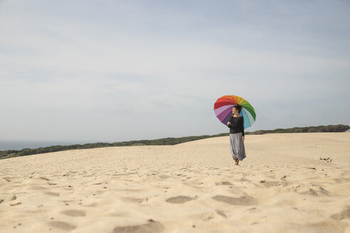 Woman with colorful umbrella standing on a dune, looking at distance - KBF00555