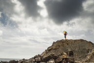 Woman with colorful umbrella standing on a hill at the beach - KBF00558