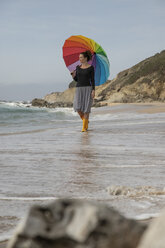 Woman with colorful umbrella standing on the beach - KBF00561