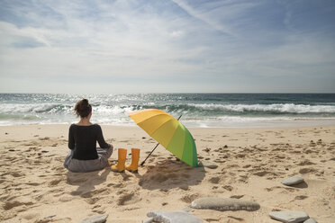 Woman with colorful umbrella sitting on the beach, rear view - KBF00564