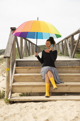 Woman with colorful umbrella standing on the beach - KBF00567