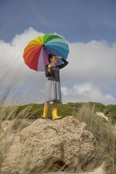 Woman with colorful umbrella standing on a rock and looking at distance - KBF00573