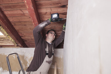 Roof insulation, worker drilling wooden board with a cordless drill - SEBF00025