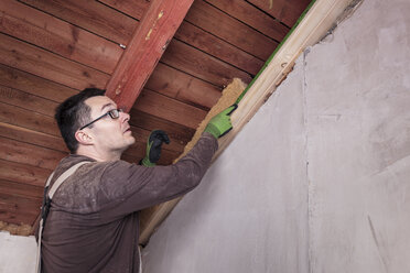Roof insulation, worker filling pitched roof with wood fibre insulation - SEBF00028