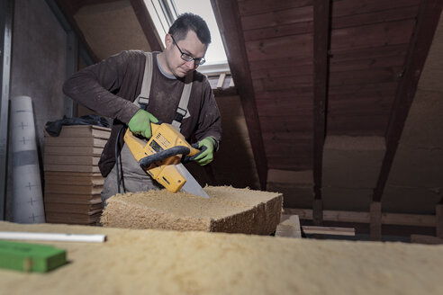 Roof insulation, worker placing wood fibre insulation at the roof - SEBF00031