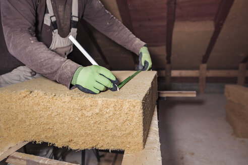 Roof insulation, worker measuring wood fibre insulation - SEBF00034