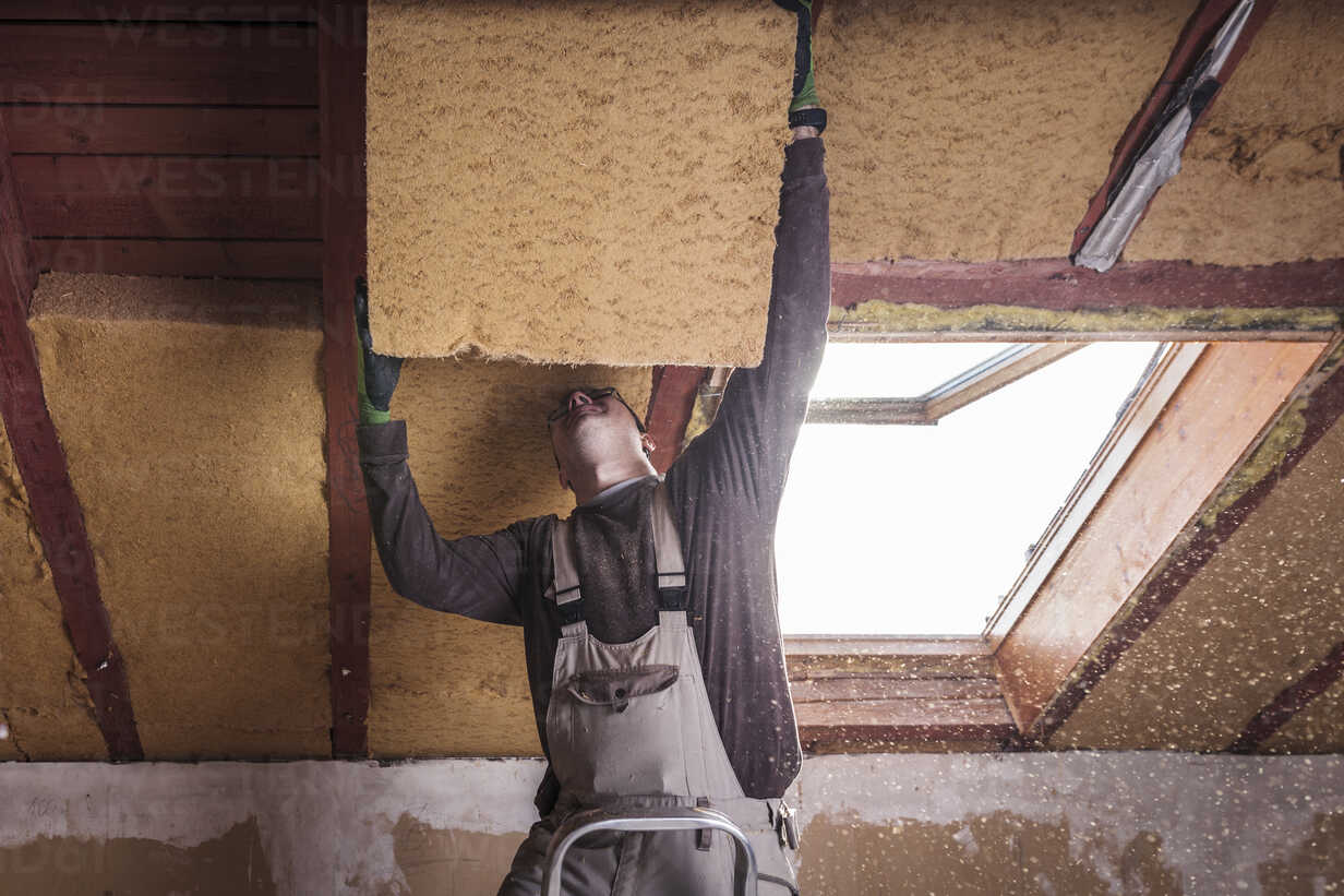 Roof insulation, worker filling pitched roof with wood fibre insulation - SEBF00037 - Sebastian Dorn/Westend61