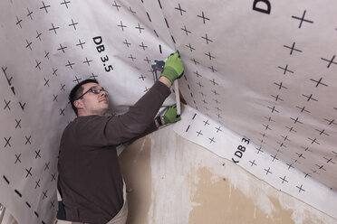 Roof insulation, worker fixing sarking membrane - SEBF00040