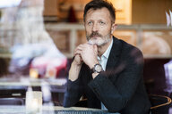 Portrait of mature businessman waiting in a coffee shop - DIGF05999