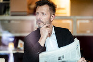 Portrait of pensive mature businessman with newspaper in a coffee shop - DIGF06002