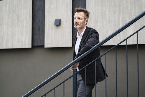 Portrait of pensive mature businessman leaning on railing - DIGF06026