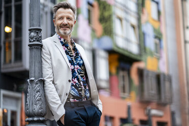 Portrait of fashionable mature man with greying beard leaning against - DIGF06047