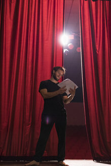 Barefoot actor standing on stage of theatre reading script - FBAF00266