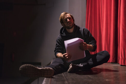 Actor sitting on stage of theatre with script - FBAF00269