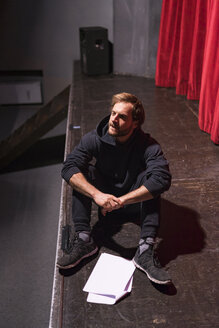 Rehearsing actor sitting on stage of theatre with script - FBAF00272