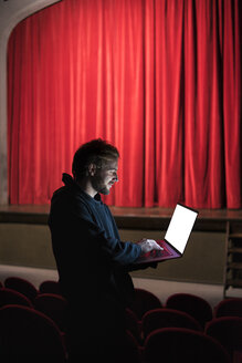 Director standing at auditorium of theatre using laptop - FBAF00284