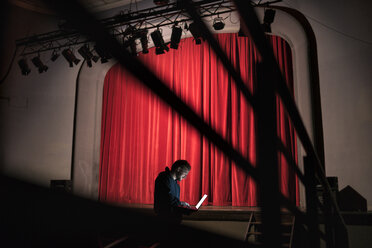 Director standing in front of stage at theatre using laptop - FBAF00287