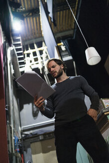 Actor with script rehearsing backstage - FBAF00290