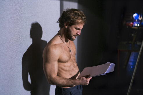 Shirtless actor looking at script at rehearsal - FBAF00305