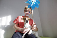 Portrait of Jack Russel Terrier with boy made up as a clown holding pin wheel - KMKF00780