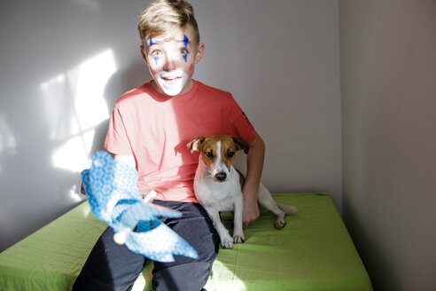 Portrait of amazed boy made up as a clown with dog and pin wheel at home - KMKF00783