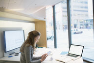 Young businesswoman using digital tablet in urban office - HEROF26994