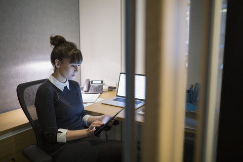Young businesswoman working late at digital tablet - HEROF27000
