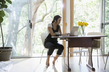 Woman working at laptop at dining table - HEROF27105