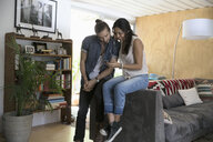 Young couple sharing headphones listening to music on mp3 player in living room - HEROF27108