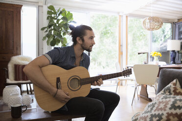 Young man playing guitar in living room - HEROF27114
