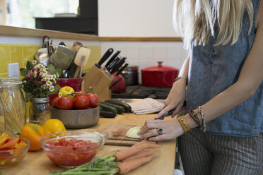 Young woman slicing vegetables in kitchen - HEROF27117