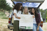 Young women looking at map at back of car - HEROF27132