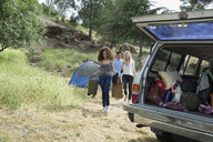 Young friends loading camping equipment in car - HEROF27135