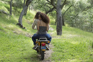 Young couple riding motorcycle on path in woods - HEROF27138