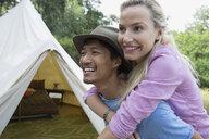 Young couple piggybacking outside camping yurt - HEROF27144