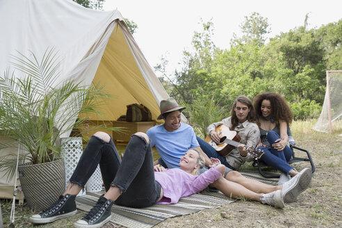 Young friends relaxing playing guitar outside camping yurt - HEROF27147