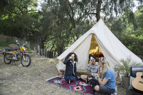 Young friends playing card game outside camping yurt - HEROF27150