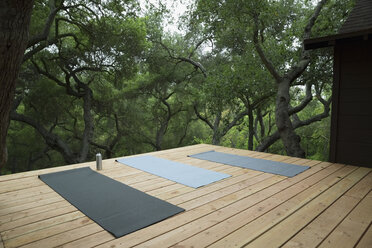 Yoga mats on deck surrounded by trees - HEROF27156