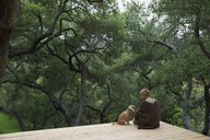 Woman and dog sitting on deck surrounded by trees - HEROF27159