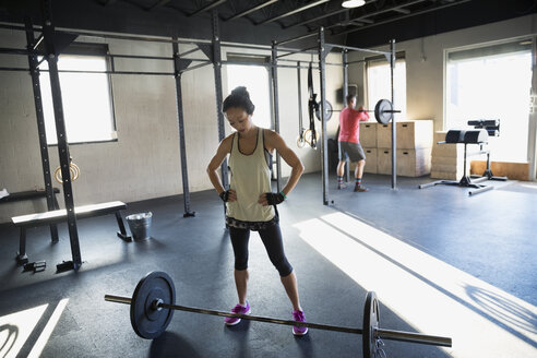 Woman preparing to to weight lift barbell gym - HEROF27177