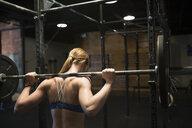 Woman weightlifting at barbell rack at gym - HEROF27204