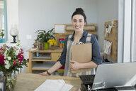 Portrait confident florist with clipboard in flower shop - HEROF27261