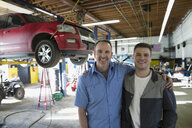 Portrait smiling father son mechanics auto repair shop - HEROF27270