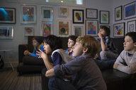 Surprised boys watching TV in living room - HEROF27282