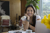 Portrait smiling woman working from home - HEROF27288