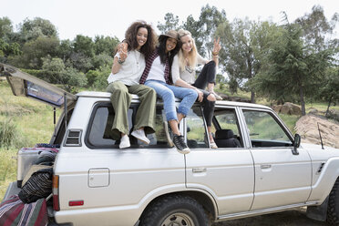 Portrait smiling young women gesturing peace sign on top of car - HEROF27300