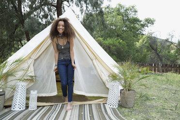 Portrait smiling young woman in camping yurt doorway - HEROF27306