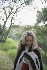 Smiling young woman wrapped in a blanket in woods - HEROF27312