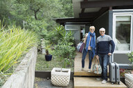 Portrait mature couple with suitcases arriving at vacation rental - HEROF27321
